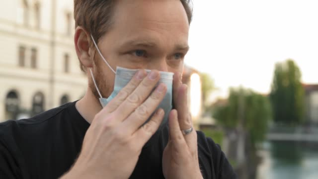 Caucasian Man Putting On Face Mask In The City video