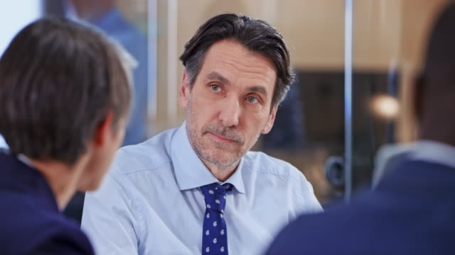 Caucasian man talking with his colleagues in a meeting