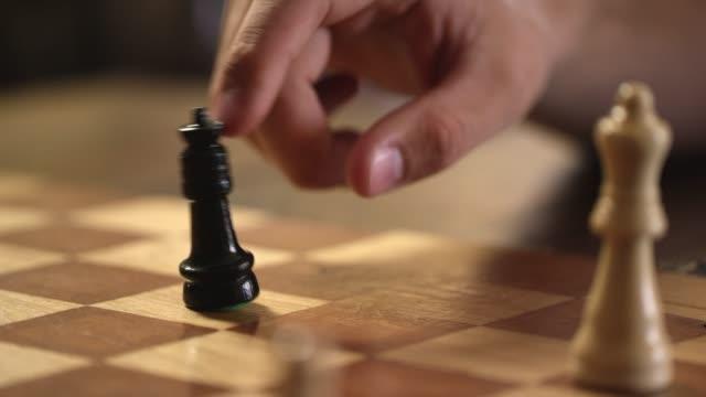 ein kaukasischer mann kippt um seines gegners königin in einer partie schach - könig schachfigur stock-videos und b-roll-filmmaterial