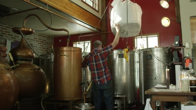 a caucasian man uses a gantry crane and winch to move a large bag of sugar cane in an indoor alcohol distillery - rum superalcolico video stock e b–roll
