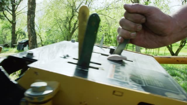 a caucasian man uses a levers on a control panel to operate machinery outdoors in an uncultivated area with trees on a sunny day - leva video stock e b–roll