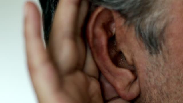 Caucasian man with hand cupped on ear listening Man uses his hands as aid, trying to hear what is being spoken. Hearing loss. Gossip. Eavesdropping. ear stock videos & royalty-free footage