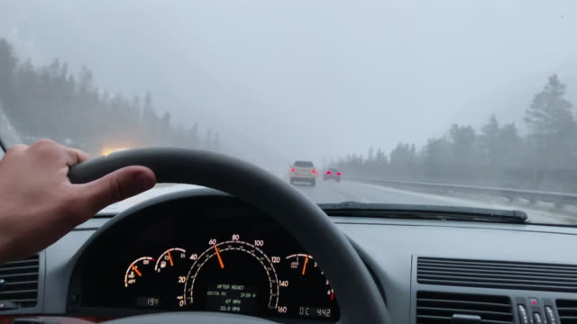 A Caucasian Man with His Hand on the Steering Wheel Drives on Interstate 70 in the Rocky Mountains of Colorado in Under an Overcast Sky in Winter