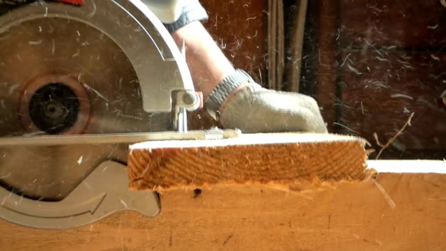 Caucasian man working with circular saw in carpenters workshop Caucasian man working with circular saw in carpenters workshop. Hands with tool cut fresh wooden board. Sunny summer day, closeup view. Rustic scene. With original sound. plank timber stock videos & royalty-free footage