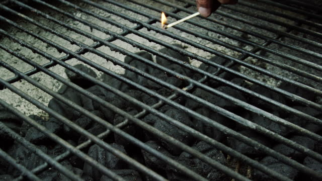 a caucasian man's hand drops a lit wooden match into a an outdoor barbecue grill, lighting the charcoal briquettes on fire in preparation for grilling - grill stock videos & royalty-free footage