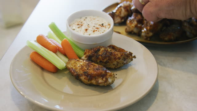 A Caucasian Man's Hand Places Grilled Chicken Wings on to a Plate Next to Carrot and Celery Sticks and a Small Bowl of Ranch Dipping Sauce A Caucasian Man's Hand Places Grilled Chicken Wings on to a Plate Next to Carrot and Celery Sticks and a Small Bowl of Ranch Dipping Sauce positioning stock videos & royalty-free footage