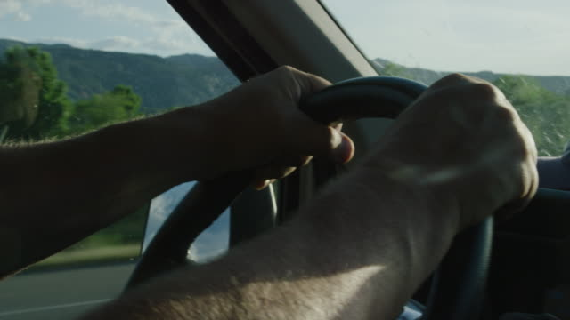 a caucasian man's hands grip the steering wheel while driving at dawn/sunset - autista mestiere video stock e b–roll