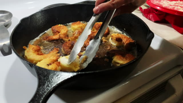 A Caucasian Man's Hands Turn over Breaded Shrimp while Frying Them in a Cast Iron Skillet in a Kitchen
