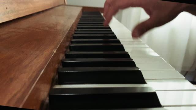 vídeos de stock e filmes b-roll de a caucasian man's right hand plays a piano's keys indoors - compositor