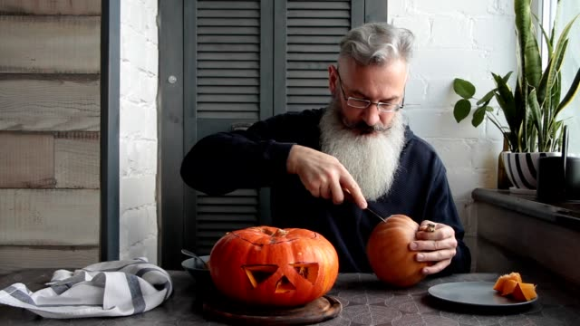 caucasian mature bearded man makes pumpkin lantern jack-o-lantern, markup and cut out his eyes and mouth, halloween concept - zucca legenaria video stock e b–roll