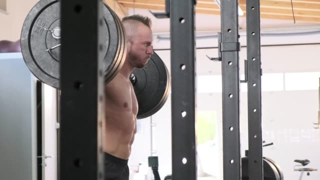 Caucasian mature man lifting heavy weights at the functional gym