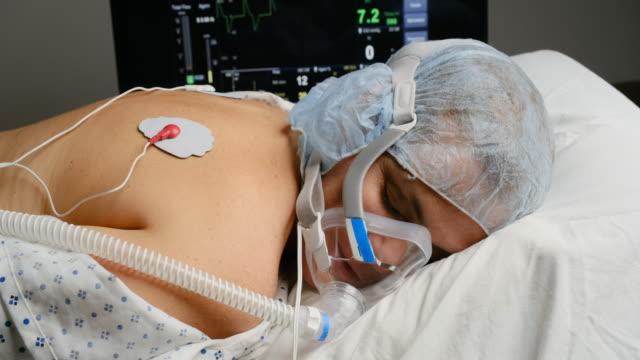 donna matura caucasica collegata a un ventilatore sdraiato sullo stomaco - china drug video stock e b–roll