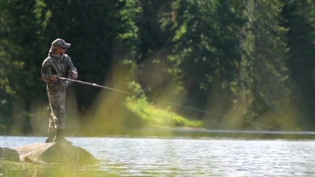 caucasian men fly fishing in slow motion - rybak filmów i materiałów b-roll