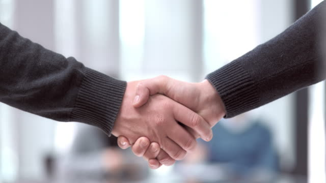 SLO MO PAN Caucasian men handshake in meeting room video