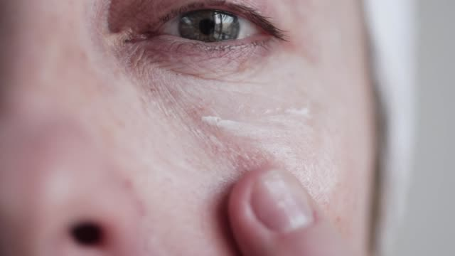 caucasian mid age woman applying cream to her face. - woman mirror video stock e b–roll