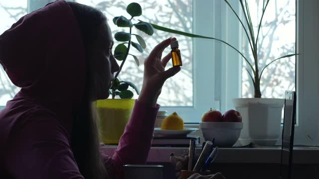 evde cam şişede d vitamini alan beyaz orta yaşlı kadın. vitamin d3 magnezyum balık yağı omega-3 takviyeleri damla. cam damlalık şişe mockup, kadın hamile yetişkin sağlık biohacking - vitamin d stok videoları ve detay görüntü çekimi
