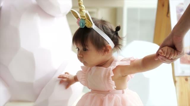 Kaukasische gemischte liebenswert Kleinkind Baby erste Schritte mit Mutter helfen bei speziellen Event wie Hochzeit oder Geburtstagsfeier – Video