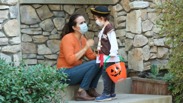 Caucasian mother put in on a protective face mask to her son before going to ask trick or treat halloween Caucasian mother put in on a protective face mask to her son before going to ask trick or treat halloween halloween covid stock videos & royalty-free footage