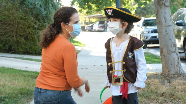 Caucasian mother put in on a protective face mask to her son before going to ask trick or treat halloween