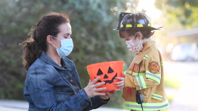 Caucasian mother put in on a protective face mask to her son before going to ask trick or treat halloween Caucasian mother put in on a protective face mask to her son before going to ask trick or treat halloween candy stock videos & royalty-free footage