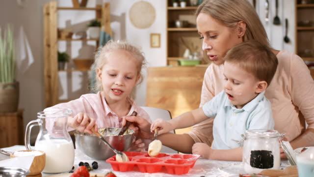 バッターでベーキングモールドを充填する子供たちと白人のお母さん - カップケーキ点の映像素材/bロール