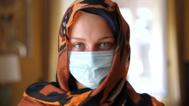caucasian muslim woman with a surgical mask looking at camera - abbigliamento religioso video stock e b–roll