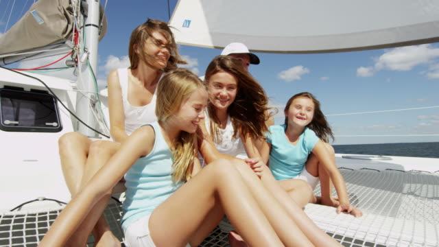 Caucasian parents and three daughters on luxury catamaran video