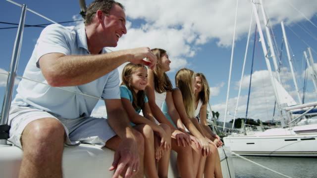 vídeos de stock, filmes e b-roll de os pais caucasianos e três filhas em iate de luxo - marina
