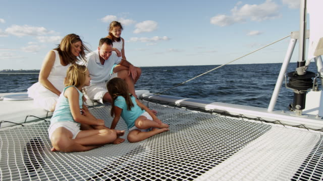 Caucasian parents three daughters together on luxury yacht video