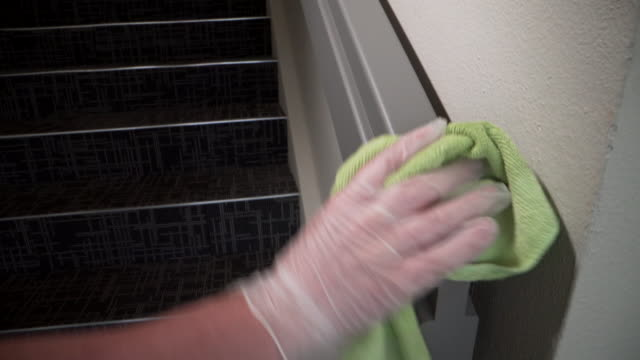 caucasian person's glove hand spraying and cleaning a wooden handrail in a public office building with alcohol-based disinfectant to prevent the spread of covid sars ncov 19 coronavirus swine flu h7n9 influenza illness during cold and flu season - parapetto barriera video stock e b–roll