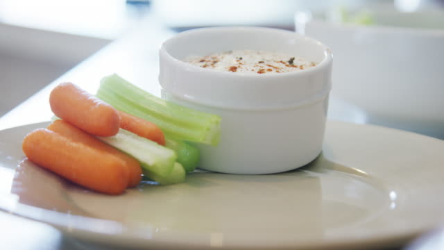 A Caucasian Person's Hand Stacks Carrot and Celery Sticks Neatly on a Plate Next to a Small Bowl of Ranch Dipping Sauce A Caucasian Person's Hand Stacks Carrot and Celery Sticks Neatly on a Plate Next to a Small Bowl of Ranch Dipping Sauce dipping sauce stock videos & royalty-free footage