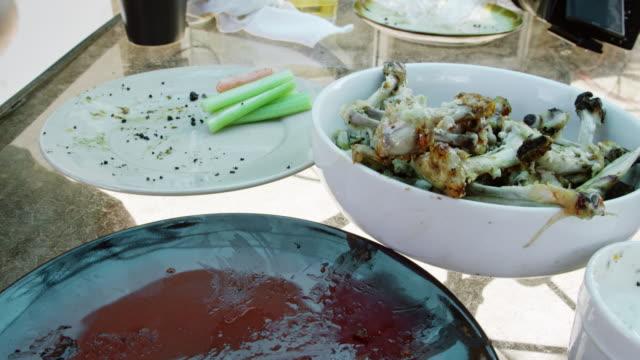 en kaukasisk persons hand kastar en kyckling wing bone i en skål på ett bord omgiven av tomma mat rätter - tallrik uppätet bildbanksvideor och videomaterial från bakom kulisserna