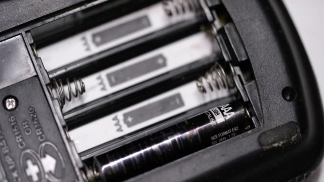 a caucasian person's hands install triple a (aaa) batteries into an electronic device - molla video stock e b–roll