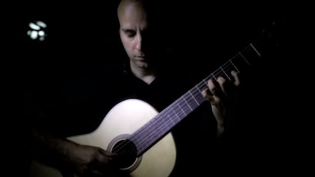 Caucasian playing a classic guitar video