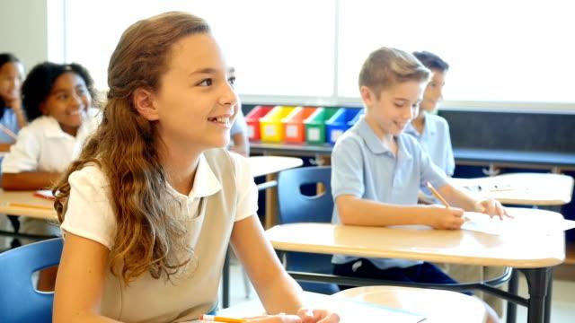 Caucasian private school student enjoys listening to her teacher during class video