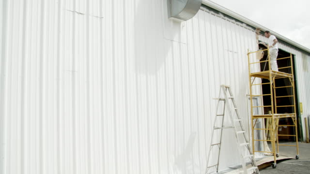 A Caucasian Professional Painter in His Thirties Uses a Paint Sprayer to Paint the Outside of a Metal Warehouse While Standing on a Scaffold under Partly Cloudy Sky A Caucasian Professional Painter in His Thirties Uses a Paint Sprayer to Paint the Outside of a Metal Warehouse While Standing on a Scaffold under Partly Cloudy Sky house painter stock videos & royalty-free footage