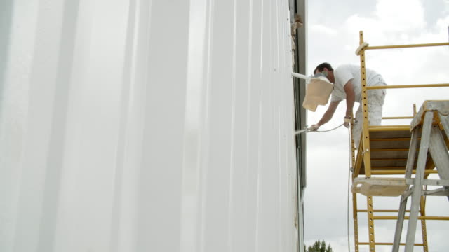 A Caucasian Professional Painter in His Thirties Uses a Paint Sprayer to Paint the Outside of a Metal Warehouse While Standing on a Scaffold under Partly Cloudy Sky