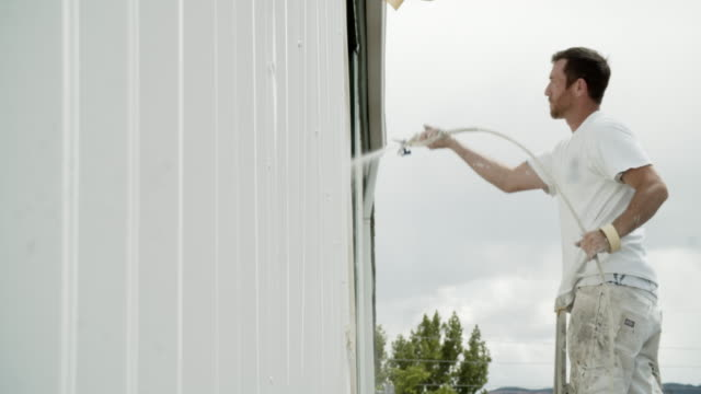 A Caucasian Professional Painter in His Thirties Uses a Paint Sprayer to Paint the Outside of a Metal Warehouse While Standing on a Ladder under Partly Cloudy Sky A Caucasian Professional Painter in His Thirties Uses a Paint Sprayer to Paint the Outside of a Metal Warehouse While Standing on a Ladder under Partly Cloudy Sky house painter stock videos & royalty-free footage