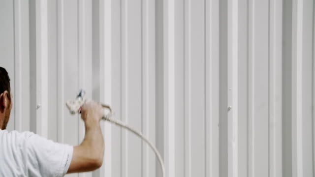 A Caucasian Professional Painter in His Thirties Uses a Paint Sprayer to Paint the Outside of a Metal Warehouse A Caucasian Professional Painter in His Thirties Uses a Paint Sprayer to Paint the Outside of a Metal Warehouse house painter stock videos & royalty-free footage
