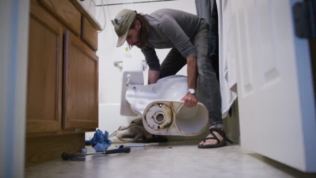 A Caucasian Repairman in His Forties with a Beard Picks Up a Toilet Resting on Its Side and Sets It Upright in an Indoor Domestic Bathroom