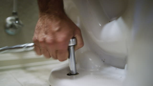 A Caucasian Repairman Uses a Socket Wrench to Ratchet the Nut on to a Toilet's Flange Bolt in an Indoor Domestic Bathroom