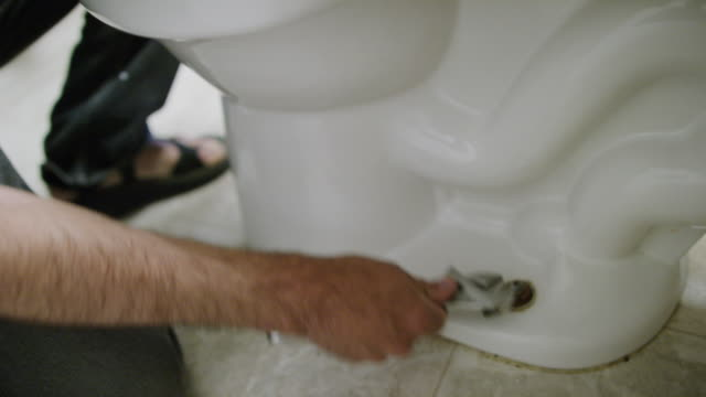 A Caucasian Repairman Uses an Adjustable Wrench to Loosen the Nut Bolting the Toilet to the Floor in an Indoor Domestic Bathroom