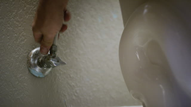 A Caucasian Repairman Uses His Fingers and an Adjustable Wrench to Connect a Toilet Hose to a Stop Valve on the Wall of an Indoor Domestic Bathroom