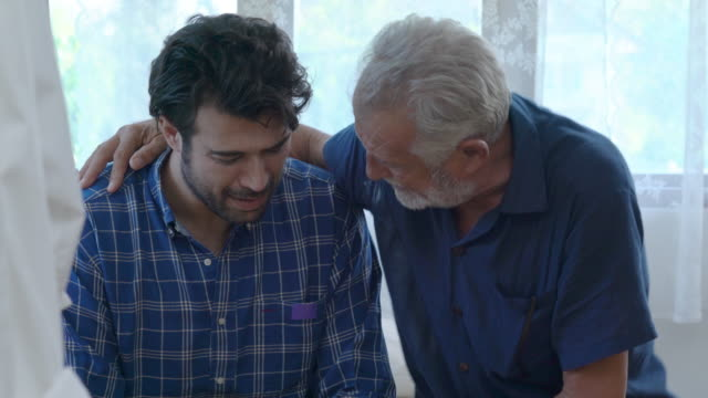 vídeos de stock e filmes b-roll de 4k caucasian senior man father comforting his depressed adult son in the bedroom. old age dad hugging and consoling sadness and crying son with love. mental health, healthcare and social issue concept - confortável