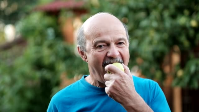 caucasian senior man in blue tshirt eating fresh apple outdoor - mordere video stock e b–roll