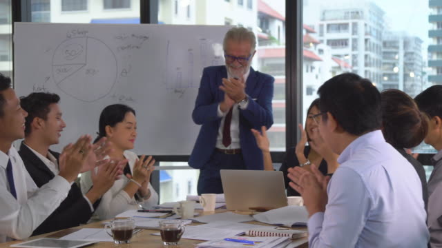 vídeos de stock e filmes b-roll de caucasian senior manager and asian businesspeople applauding for celebration to success work while meeting in modern workplace, pan shot - training
