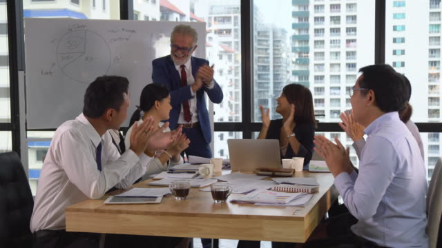 vídeos de stock e filmes b-roll de caucasian senior manager coaching asian businesspeople and applauding for celebration to success work in modern workplace - training