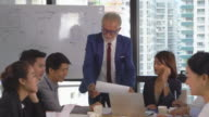 istock Caucasian senior manager coaching to asian businesspeople while meeting in modern workplace, tilt shot 1160823865