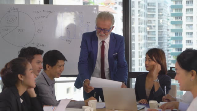 Caucasian senior manager coaching to asian businesspeople while meeting in modern workplace, tilt shot