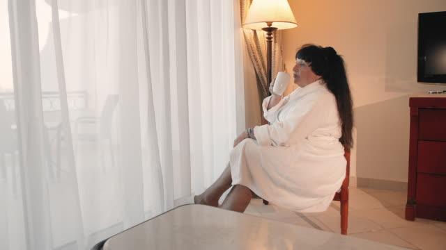 vidéos et rushes de femme aînée caucasienne buvant le café le matin près d'une grande fenêtre panoramique dans une robe blanche de terry. ralenti - peignoir